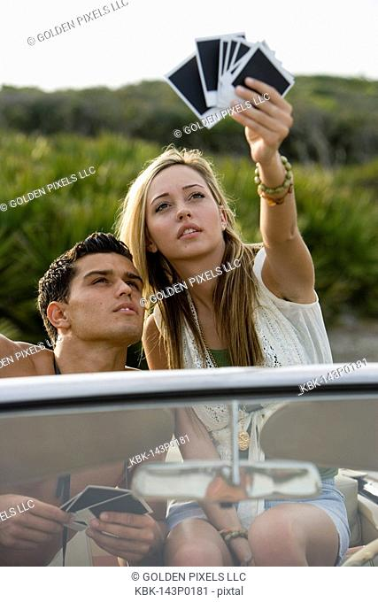 Young couple sitting in antique convertible car looking at photographs