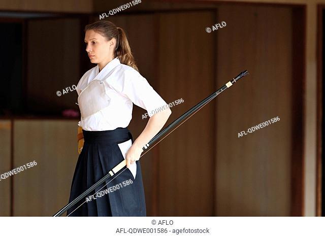 Caucasian woman practicing traditional Kyudo Japanese archery