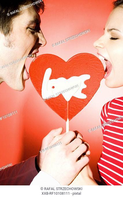 Couple eating heart shaped lollipop