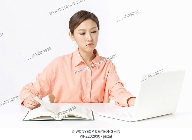 Adult woman in orange shirt seated at desk working on a laptop and holding a book page with frowned face