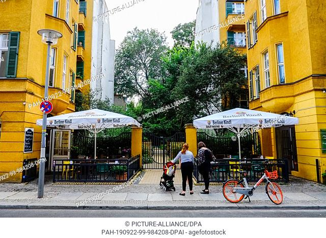 18 July 2019, Berlin: Two women with a pram stand in front of a beer garden in the Große Hamburger Straße in the Mitte district