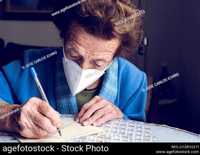 Senior woman writing on paper at home