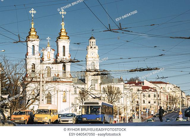 Vitebsk, Belarus. Traffic At Lenina Street And Landmarks On Background Church Of The Resurrection Of Christ On The Market Square And City Hall In Sunny Winter...