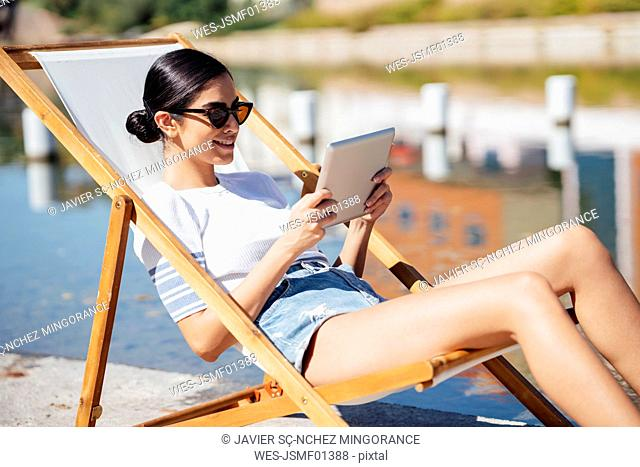 Smiling young woman sitting in a deckchair using tablet