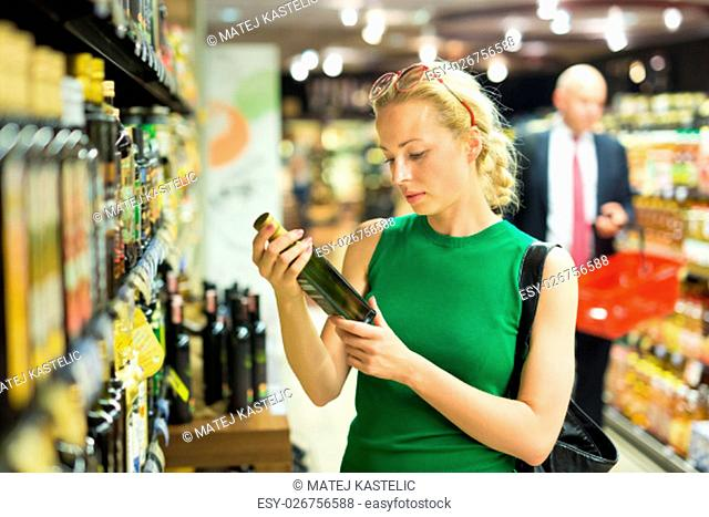 Beautiful caucasian woman shopping groceries at supermarket