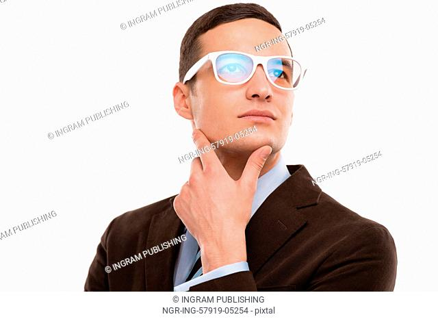 Young thoughtful businessman wearing glasses and holding chin on hand on white background