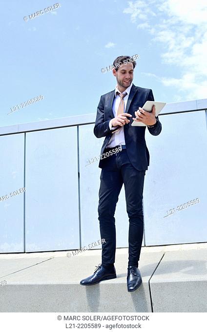 Businessman using a tablet, standing, near a wall outdoors