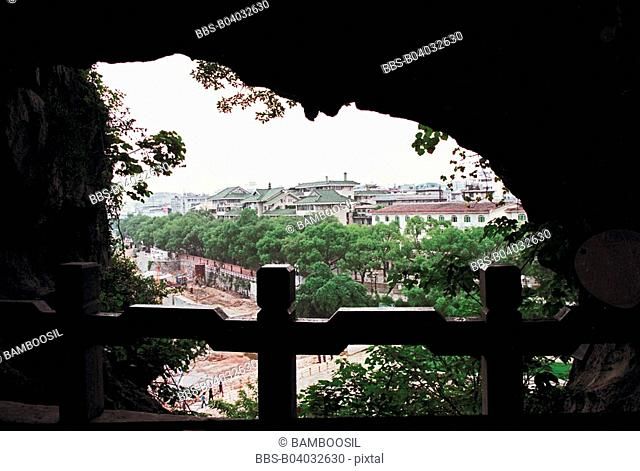 View of houses from cave with wooden railing, Guilin City, Guangxi Zhuang Nationality Autonomous Region of People's Republic of China