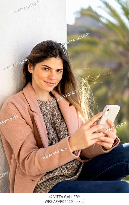 Portrait of smiling young woman holding cell phone