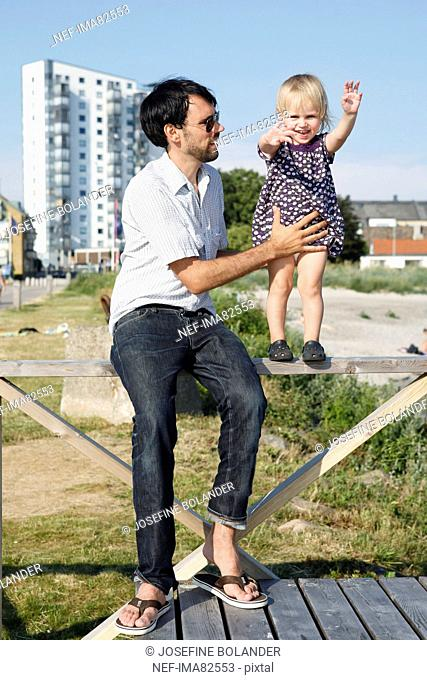 Daughter standing on railings, father holding
