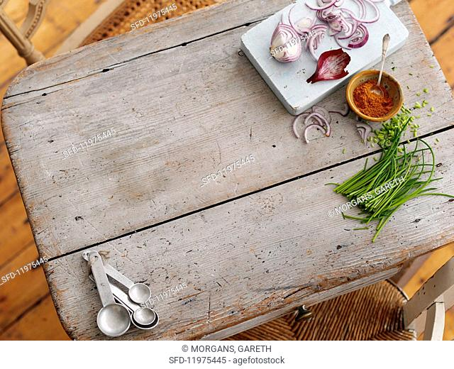 Chives, red onions, paprika powder and measuring spoons on a wooden board