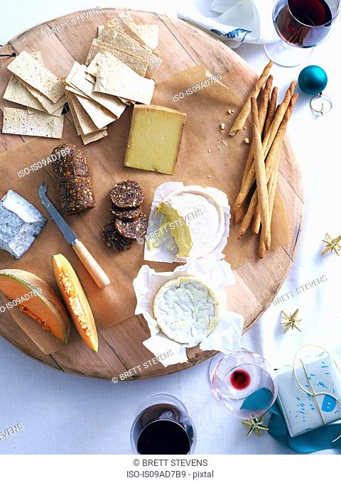 Cheese platter with breads and rock melon on decorated table