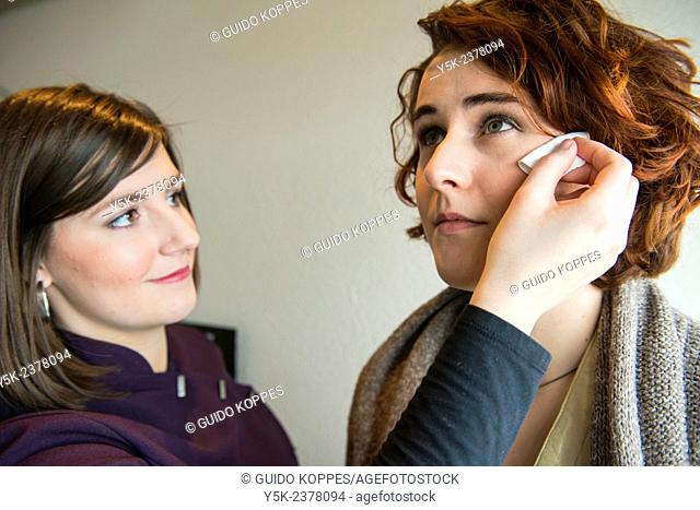 Tilburg, Netherlands. Young, brunette beautician applying male up to her customers face