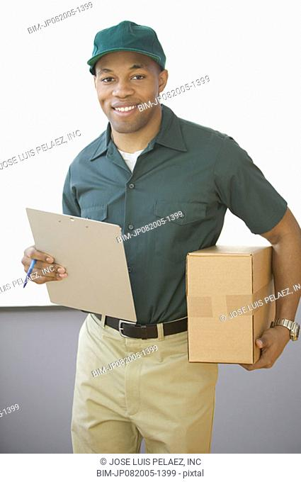 Portrait of delivery man holding box and clip board