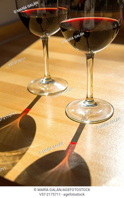 Two glasses of red wine and its shadows on the wooden table