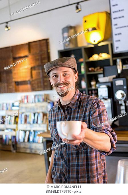 Caucasian barista serving coffee in cafe