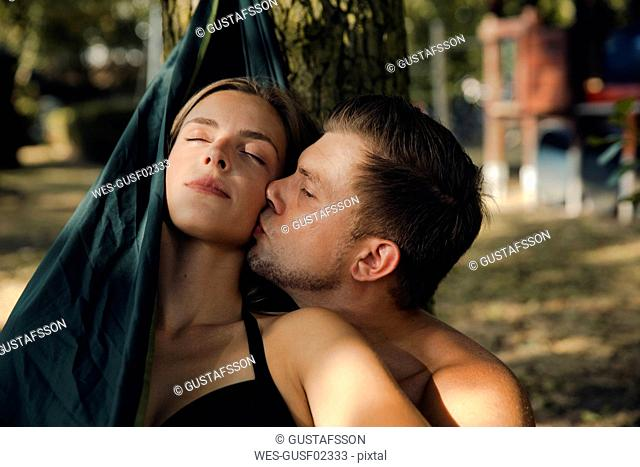 Couple relaxing in hammock by the lake, kissing