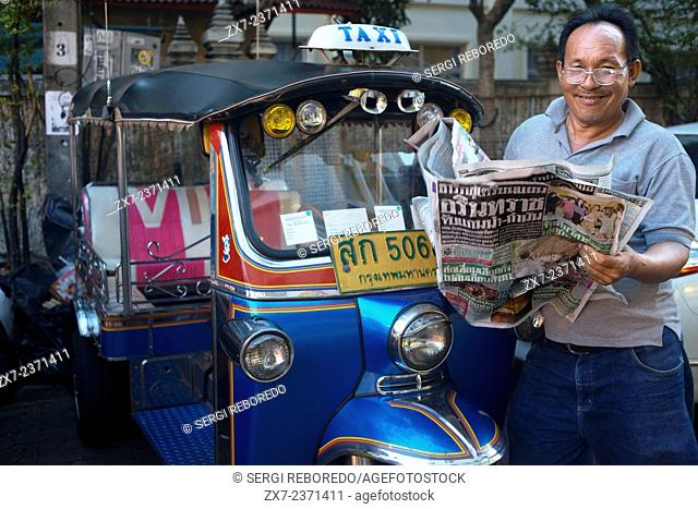 Tuk tuk driver reading the newpaper. Tuk-tuks or 'sam lor' (three-wheeled) used to be everyone's favourite way of getting around Bangkok before the BTS