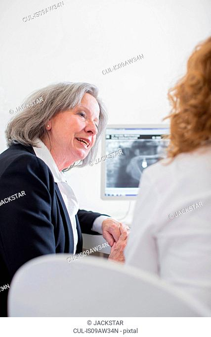 Senior woman discussing x-ray image on computer screen