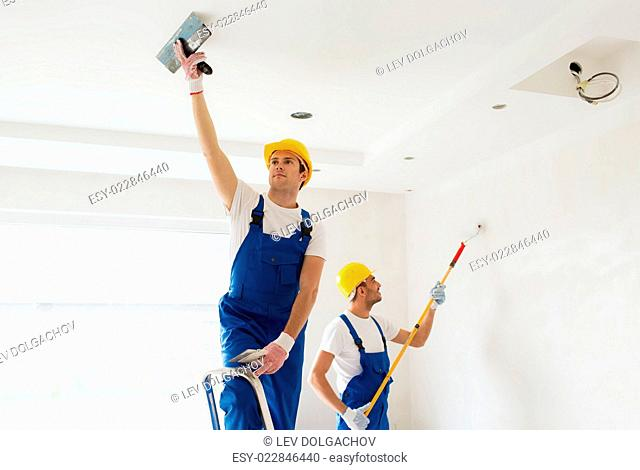business, building, teamwork and people concept - group of builders in hardhats with plastering tools indoors