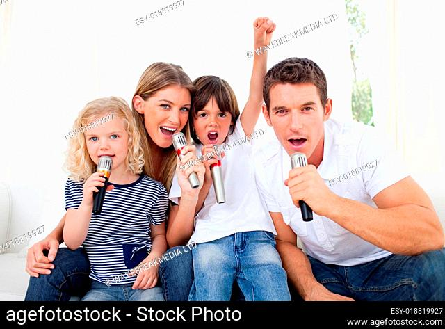 Portrait of a lively family singing through microphone
