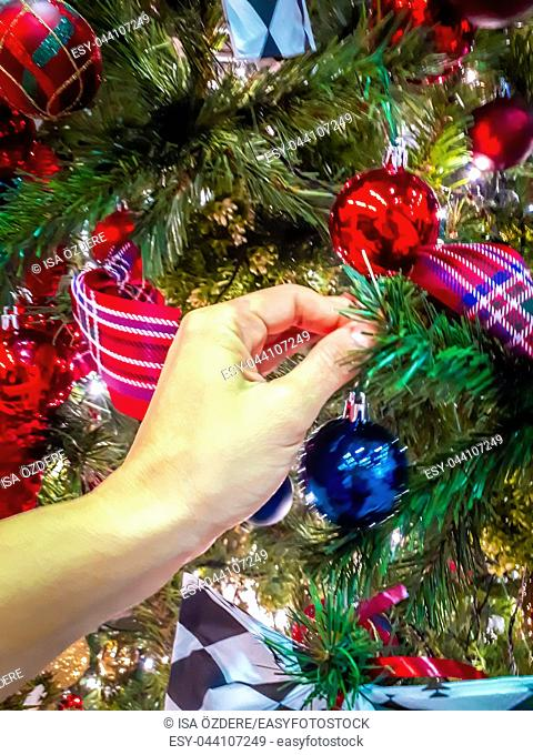 Woman hand decorates Christmas tree with different kind of decorations