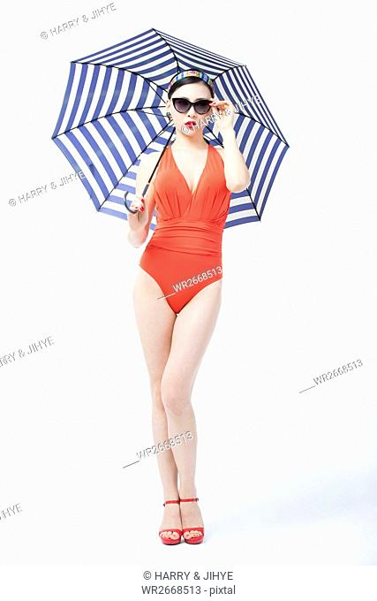 Young woman in orange swimsuit and sunglasses posing holding umbrella