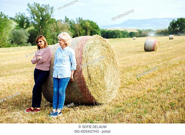 Two mature female friends leaning against straw bale, Tuscany, Italy