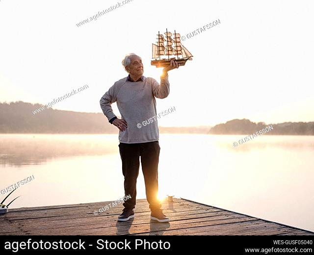Man holding sailing ship while standing with hand on hip against lake
