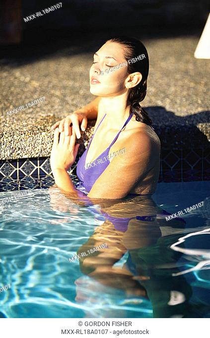 Young woman in swimming pool, resting against edge in the sun - private pool, White Rock