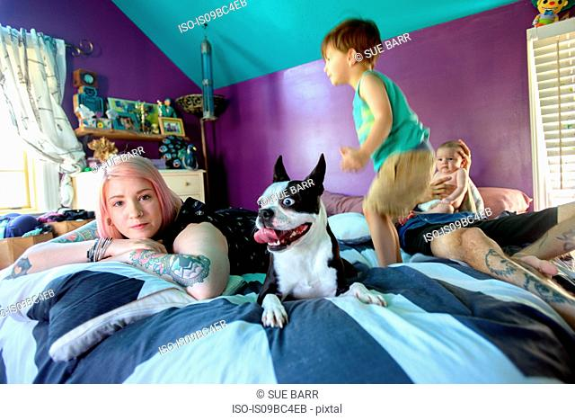 Family and pet dog on bed in bedroom