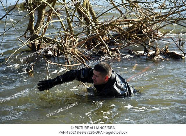 18 February 2019, Hessen, Guxhagen: A police diver in a wetsuit searches the banks of the Fulda River. The search for the five-year-old girl who disappeared...