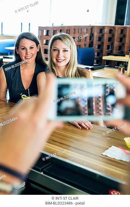 Caucasian bartender taking cell phone photograph of customers