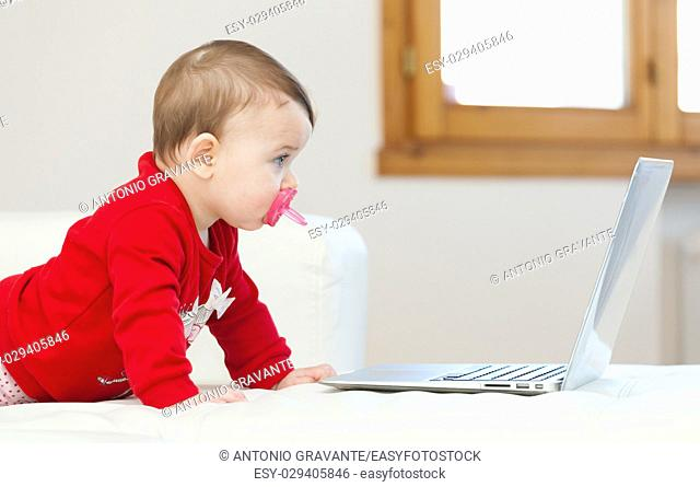 Eight months old baby girl using a laptop on the couch at home