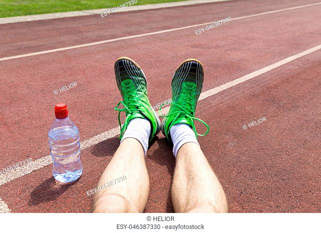 An exhausted athlete on a running track wearing broken green running shoes with big holes in the sole