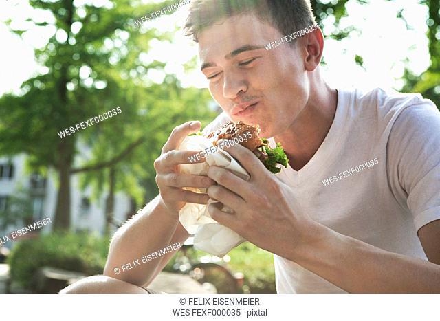 Young man eating hamburger