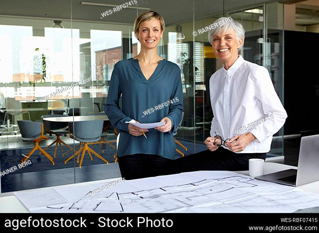 Portrait of two confident businesswomen with construction plan in office