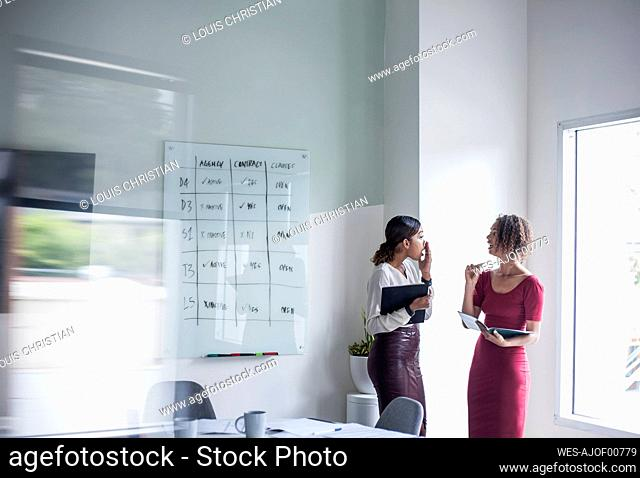 Female entrepreneur with colleague discussing while standing in office