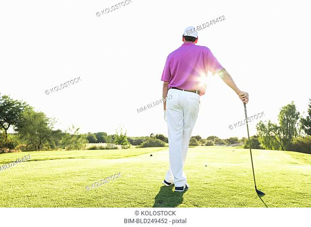 Hispanic golfer leaning on golf club on golf course