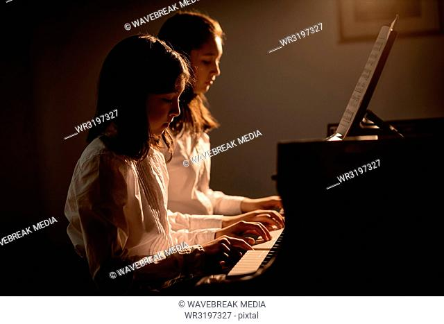 Siblings playing piano in music school