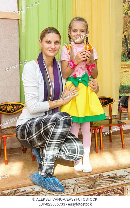 Mum with a six-year daughter who is holding an apple in his hand on a matinee in kindergarten