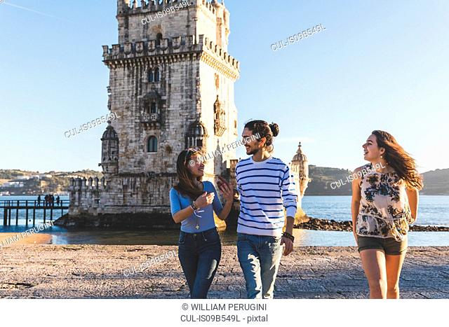 Three friends, walking on beach, Belem Tower in background, Lisbon, Portugal