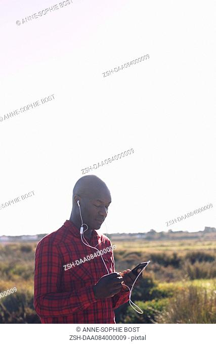 Man using smartphone and earphones outdoors