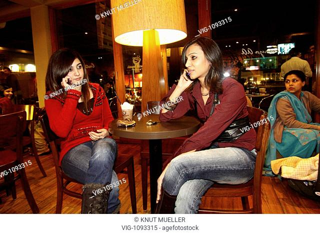 Modern young women wearing jeans maker a phone call with mobile in the business centre of Lahore. - Lahore, Punjab, PAKISTAN, 07/12/2008
