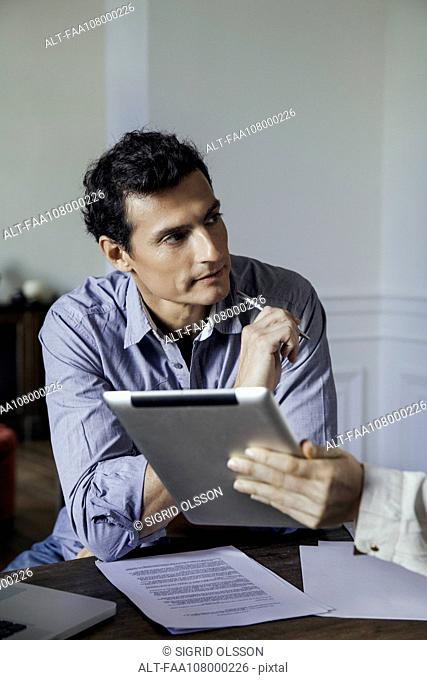 Man listening as colleague shows him something on a digital tablet