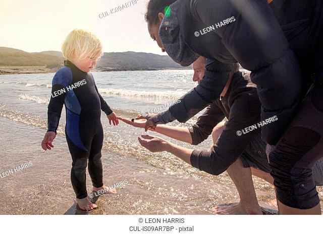 Boy and parents on beach, Loch Eishort, Isle of Skye, Scotland