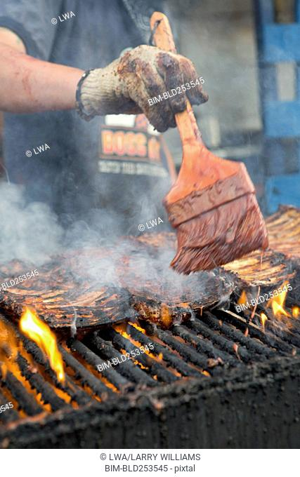 Man brushing barbecue sauce on ribs cooking on grille