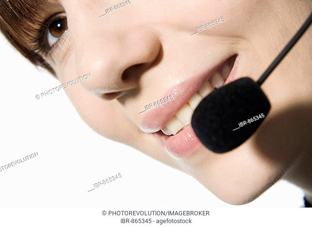Close-up of the face of a young woman on the phone using a headset