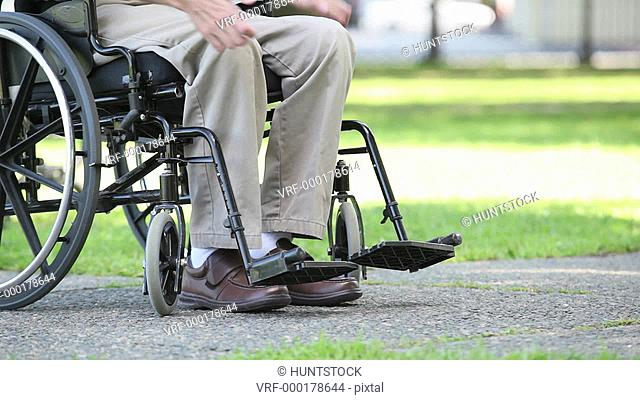 Man in a wheelchair with Friedreich's Ataxia trying to adjust foot pedals with atrophied hands