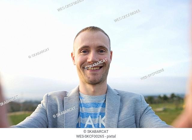 Portrait of smiling man taking selfie